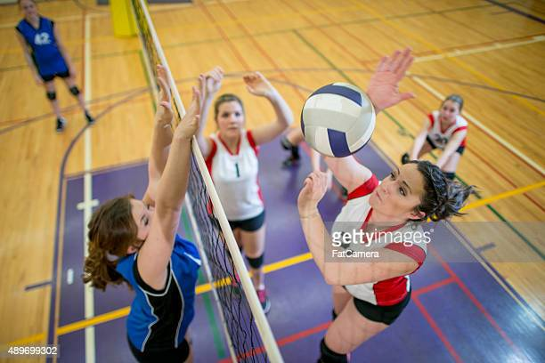 women spiking and blocking a volleyball - team sport stock pictures, royalty-free photos & images