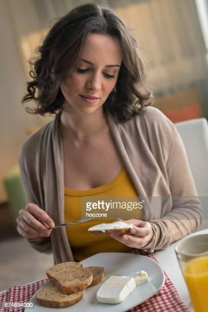 Mujeres separarse queso crema sobre rebanada de pan y comer en casa