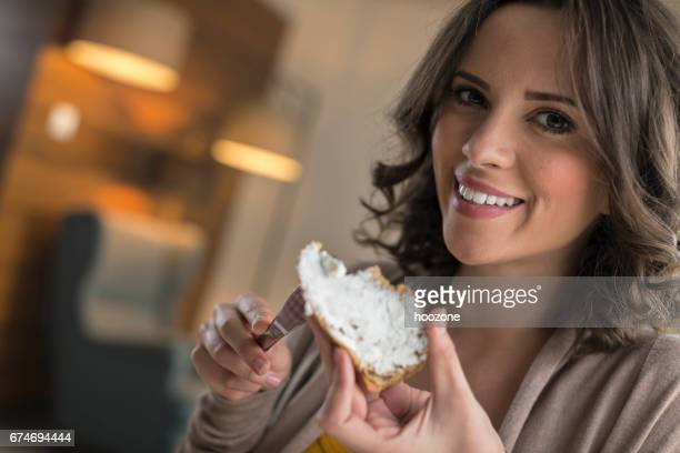 women spreading cream cheese on slice of bread and eating at home - spread food stock pictures, royalty-free photos & images