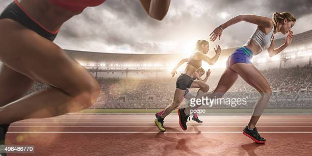 women sprinters during race on outdoor athletics track in arena - atletiek stockfoto's en -beelden