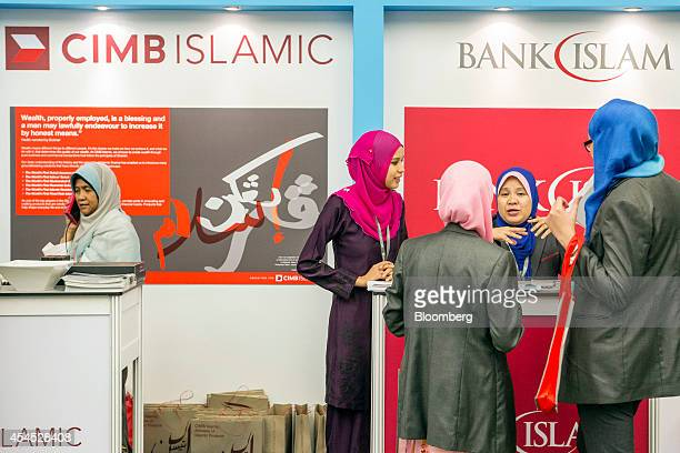 Women stand at the CIMB Islamic Banking Bhd and the Bank Islam Malaysia Bhd booths at the Global Islamic Finance Forum in Kuala Lumpur Malaysia on...