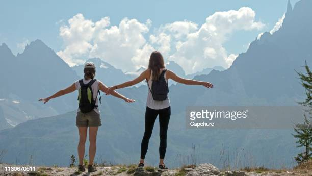 2 women stand at the mountain top looking across the valley at the high peaks of the alps. their arms are out stretched in the sunshine looking at the view. - haute savoie fotografías e imágenes de stock
