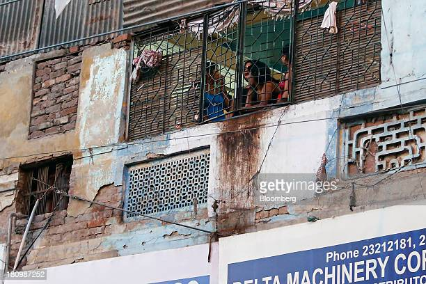 Women stand by a window in a building on Garstin Bastion Road in New Delhi India on Wednesday Sept 18 2013 Districts such as Bharatpur Rajastan where...