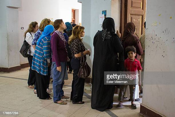 CONTENT] Women stand in line to cast their vote at a polling station in Cairo for the second round of the presidential elections