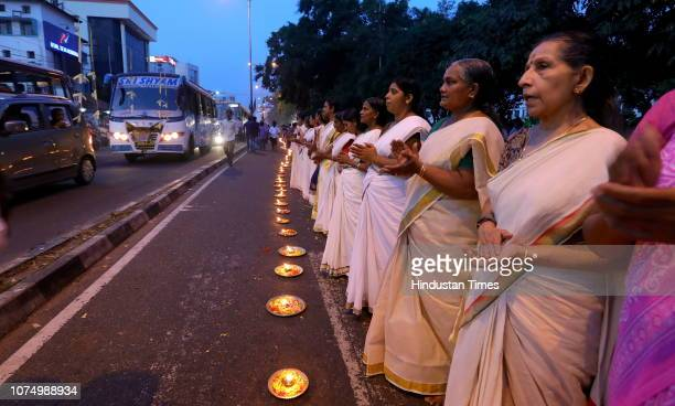 Women stand near oil lamps by a roadside during the Ayyappa Jyoti campaign against the Supreme Court verdict allowing the entry of women into...