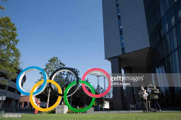 Women stand next to the Olympic Rings installation in front of the Japan Olympic Museum in Shinjuku. Japanese start thinking that it would be the...