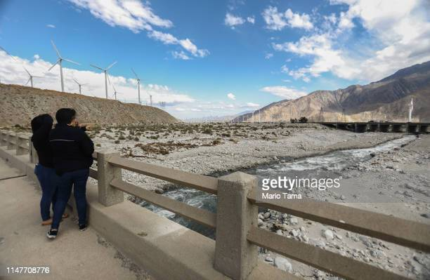 Women stand on a bridge over the Whitewater River a key water source for the Coachella Valley on May 6 2019 in Whitewater California California's...