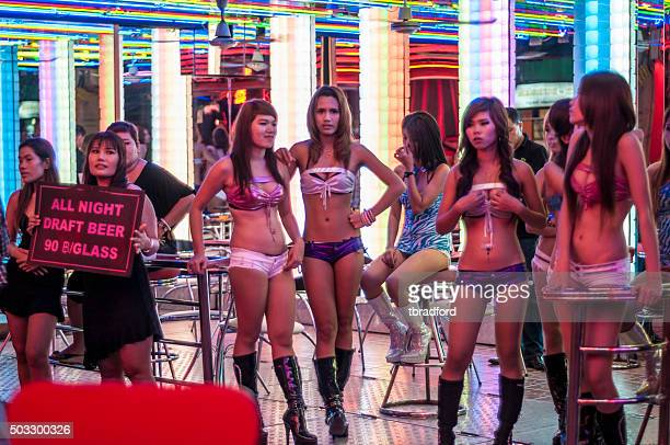 women stand outside a go-go bar in soi cowboy, bangkok - hoeren stockfoto's en -beelden