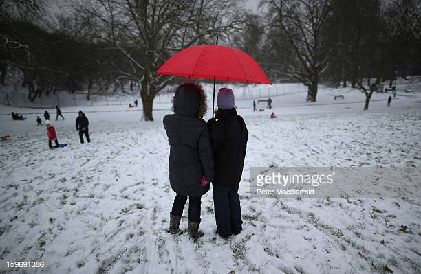 Women stand under a red umbrella as they watch their children play in fresh snow at Alexandra Palace on January 18 2013 in London England Severe...