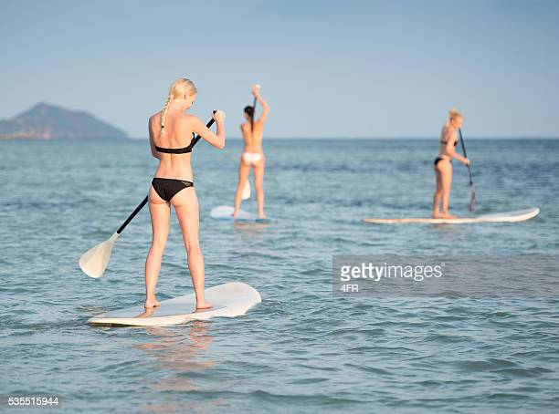 Frauen Stand-Up-Paddling (SUP) während dem Sonnenuntergang