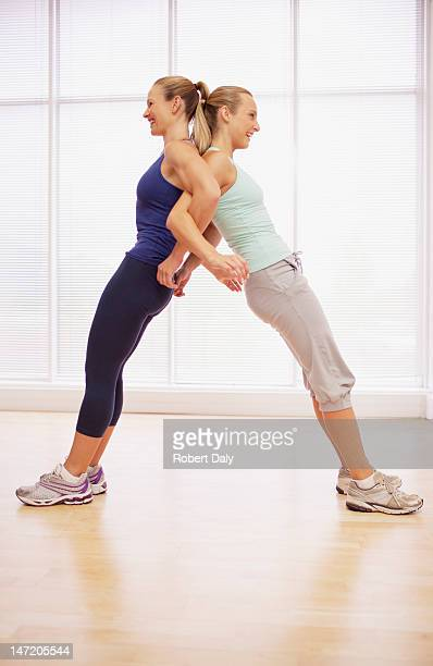Women standing back to back in fitness studio