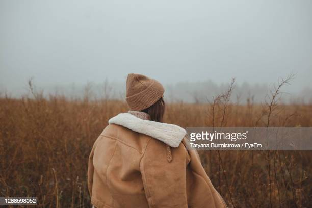 women standing in a foggy late autumn winter field against sky looking back with negative space - winter coat stock pictures, royalty-free photos & images