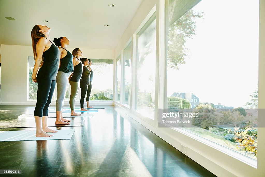 Group of women standing on yoga mats in yoga studio stretching during class