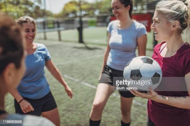 vrouwen staan op een voetbalveld - damesvoetbal stockfoto's en -beelden