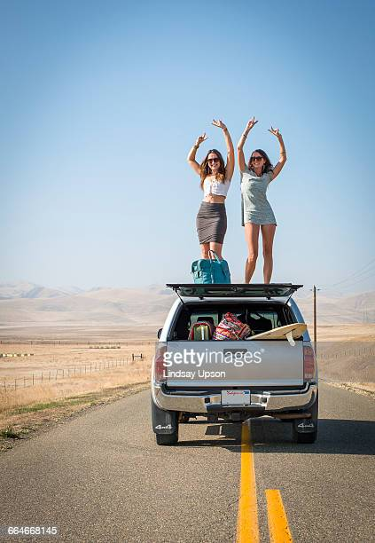 Women standing on car roof, Highway 1, California, USA