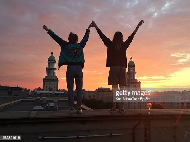 Women Standing On Roof Wall Against Dramatic Sky