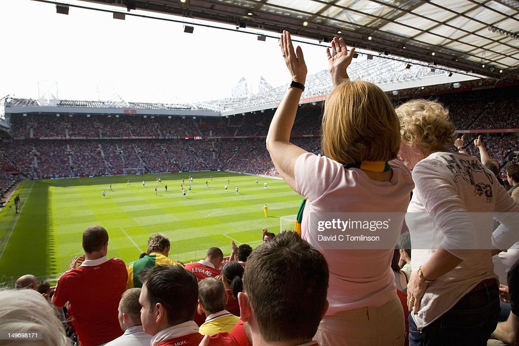 Women standing to applaud a goal during English Premiership football match between Manchester United and Fulham, Old Trafford. : Stock Photo