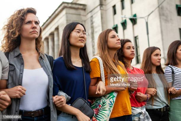 women standing together - unfairness stock pictures, royalty-free photos & images
