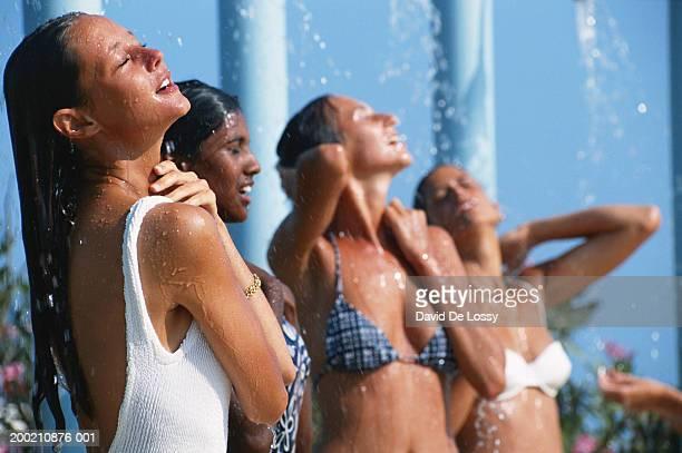 women standing under shower - femme douche photos et images de collection