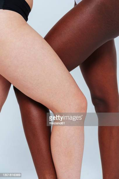 women standing with legs crossed at knee in studio - mid section stock pictures, royalty-free photos & images