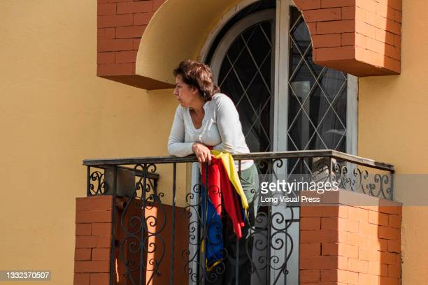 Women stands on a balcony with a Colombian flag as demonstrations ended in late-night clashes between riot police and Demonstrators as Colombia marks...