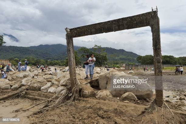 TOPSHOT Women stare at damages caused by mudslides following heavy rains in Mocoa Putumayo department southern Colombia on April 2 2017 The death...