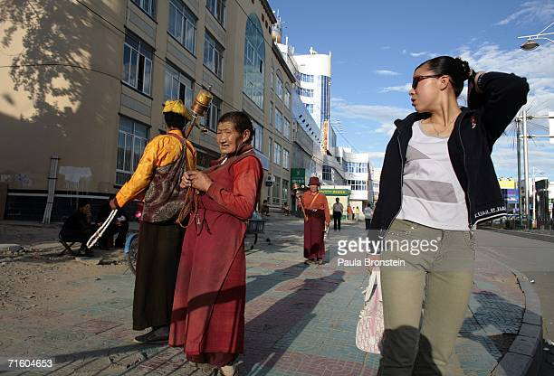 A women stares at Tibetan monks August 6 2006 in the new sectiojn of Lhasa in the Tibet Autonomous Region China Lhasa's face is ever changing as it...