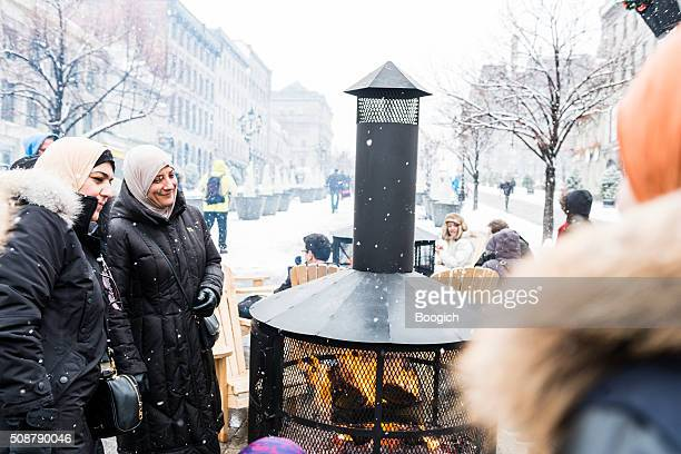 Women Stay Warm by Fire Outdoors in Old Montreal Winter