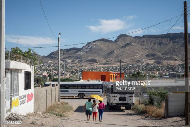 """Women staying at at Iglesia Metodista """"El Buen Pastor"""" Migrant Shelter take a walk outside of the shelter which overlooks the ubiquitous slogan on..."""