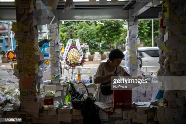 A women sticks tape to a peace of paper near a memorial set up in Honor of a man who died after falling from a scaffolding in Pacific Place while...