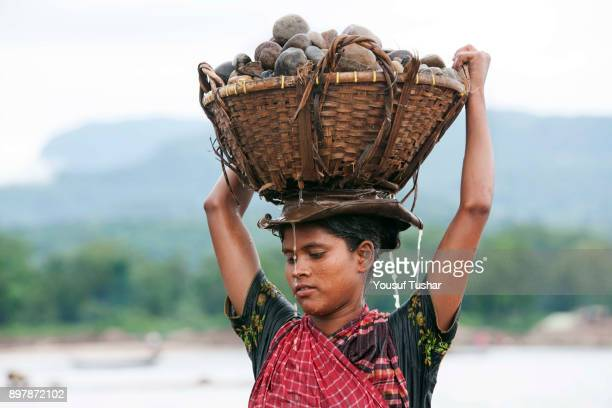 BHOLAGANJ SYLHET BANGLADESH A women stone laborer carrying stones on her head at Jaflong Stone Quarry field The crystal clear water of the Piyain...
