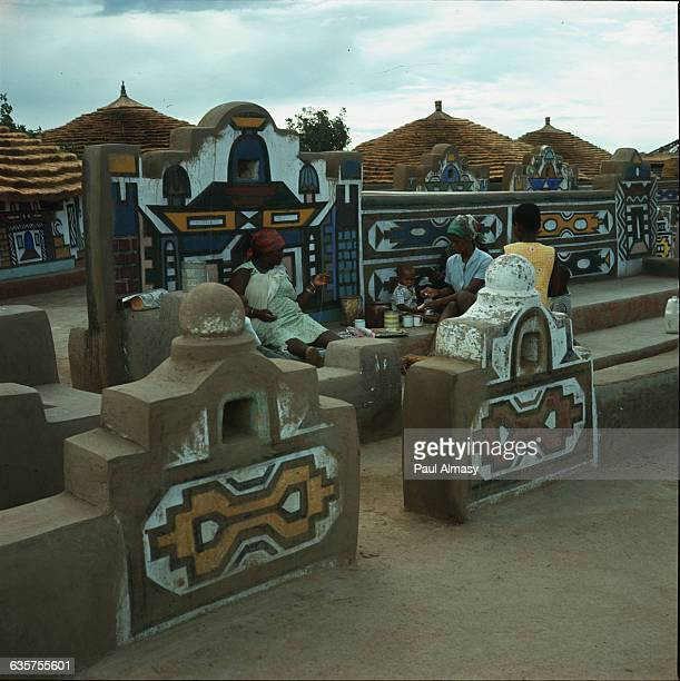 Women stop for a drink amid the brightly painted walls of Ndebele a village near the South African city of Pretoria | Location Ndebele South Africa
