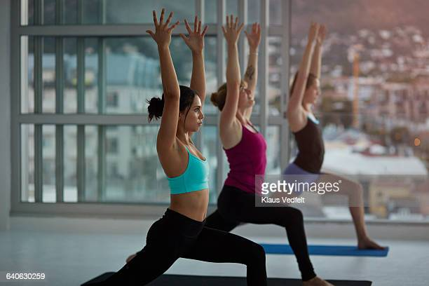 Women streching arms at yoga session