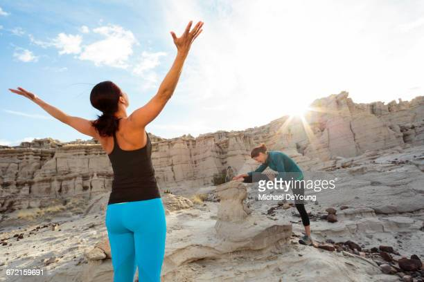 Women stretching arms and legs in canyon