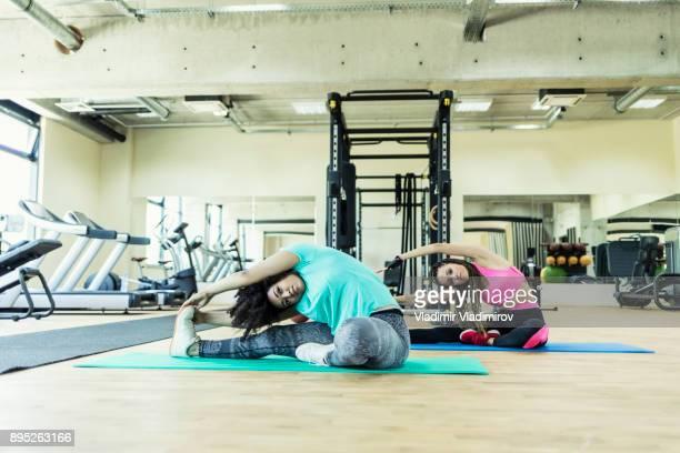 Vrouwen die zich uitstrekt in sportschool