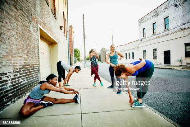 Women stretching together on sidewalk before run