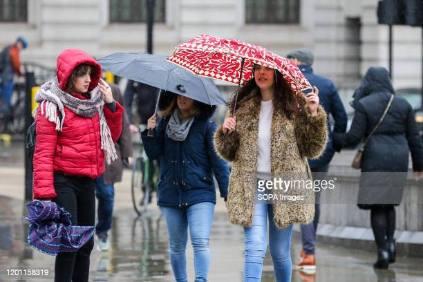 Women struggle with umbrellas in central London during wet and windy weather. Storm Dennis will bring heavy rain and strong winds across the UK...
