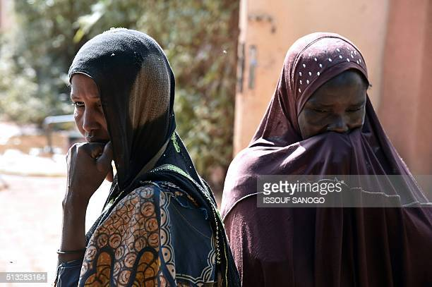 Women suffering from obstetric fistula stand outside the health centre of the DIMOL nongovernmental organisation in Niamey on February 19 2016 Niger...