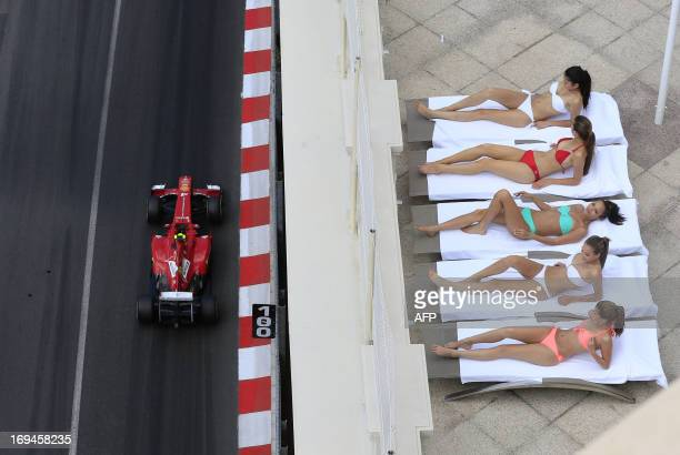Women sunbath as Ferrari's Brazilian driver Felipe Massa drives past during the third practice session at the Circuit de Monaco in Monte Carlo on May...