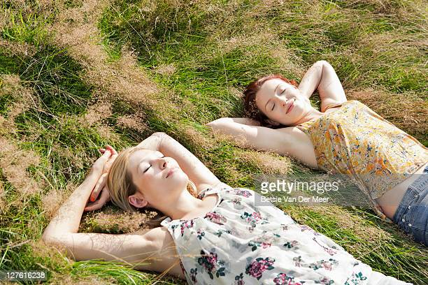 women sunbathing in field. - women sunbathing stock photos and pictures