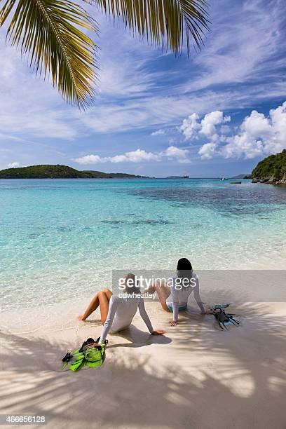 women sunbathing on a beach after snorkeling in St.John, USVI