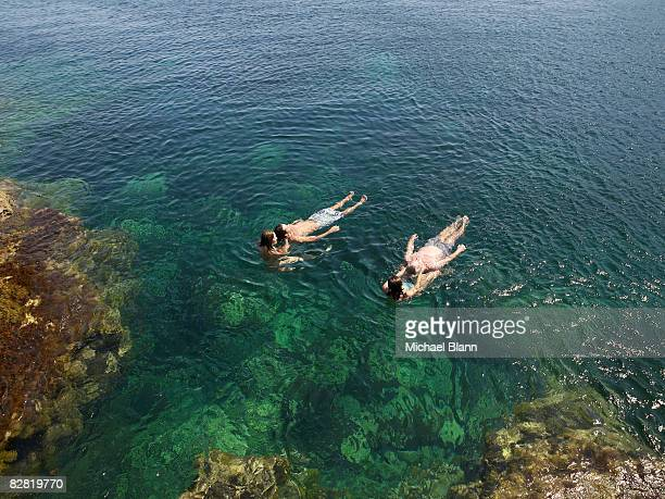 women support floating men - sea swimming stock photos and pictures