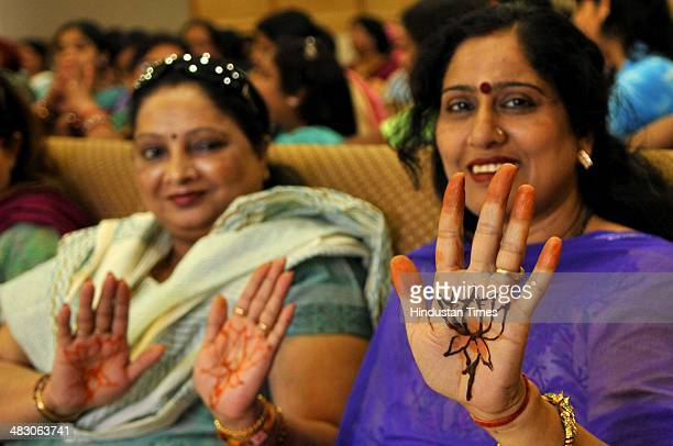 Women supporters of Bhartiya Janta Party showing their hands decorated with henna with the party symbol as they campaign in favour of BJP Prime...