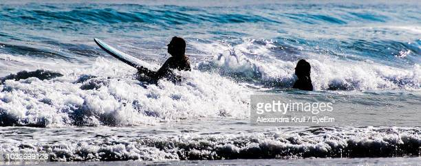 Women Surfing In Sea At Beach