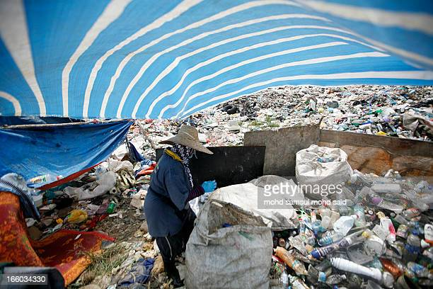 CONTENT] A women surrounded by a pile of trash scavenges for plastic for recycling at a garbage dump site in Bachok 550 kilometres northeast of Kuala...