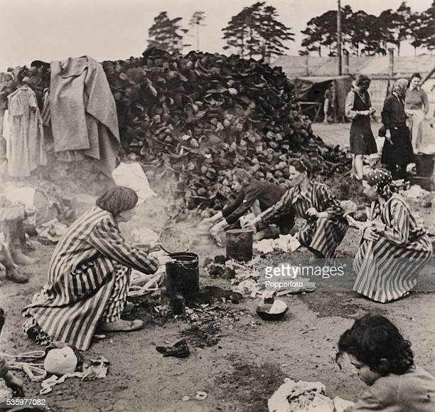 Women survivors cooking over open fires at the BergenBelsen concentration camp after it was liberated by British troops 15th April 1945 They are...