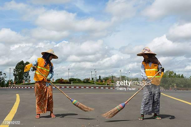 Women sweep a deserted Naypyidaw avenue