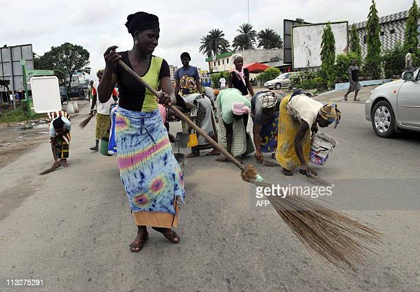 Women sweep a street of the popular Marcoury district of Abidjan during a 'Clean City' operation launched in all Abidjan districts under the control...