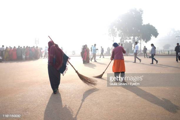 women sweeping street in city - sweeping stock pictures, royalty-free photos & images