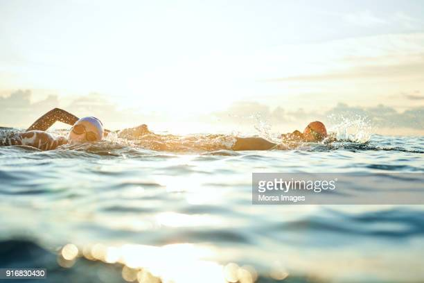 Women swimming in sea against sky during sunset